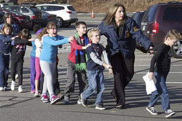 Connecticut State Police lead children from the Sandy Hook Elementary School in Newtown, Conn., after a shooting there Friday, Dec. 14, 2012. A web-only photo courtesy of Shannon Hicks/The Newtown Bee.