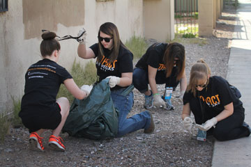 (From left) Becca Brazell, Bekah Rock, Amy Pazan-Ellensburg and Katharine Smith pick up metal, broken glass and other debris during volunteer cleanup with Impact 2013 in Las Vegas. A UMNS photo by Kats Barry.