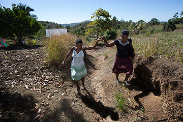 Yolande Gabriel (right) helps expectant mother Dieula Alrich make her way along a rural trail near Mizak, Haiti.