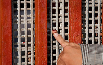 Tightly-spaced wire mesh prevents more than fingertip contact across the border between Tijuana, Mexico, and the U.S.