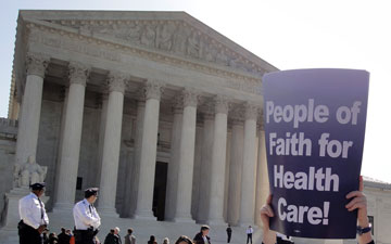 A demonstrator holds a sign in front of the U.S. Supreme Court in favor of the U.S. healthcare legislation, which the court upheld last year. A 2012 file photo by Michelle Whittaker/ United Methodist Board of Church and Society.