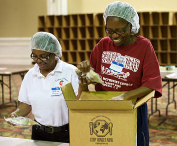 Volunteers pack boxes during the Stop Hunger Now event.