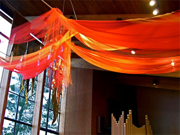 Using red fabric draped above the congregation can create a dramatic symbol of Pentecost in worship. Photo courtesy of Marcia McFee.