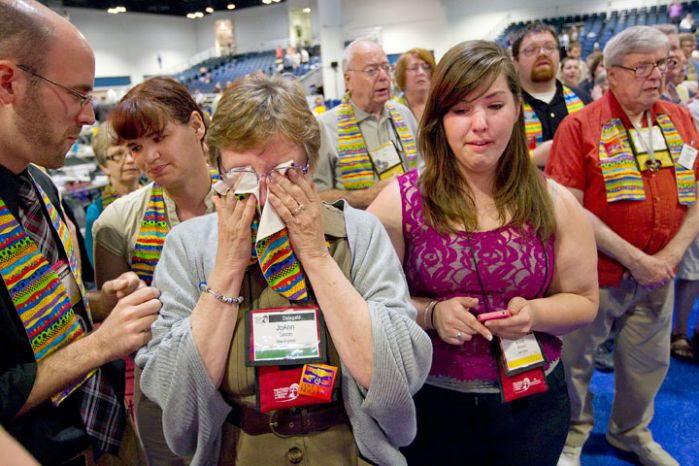 Jo Ann Carlotto, delegate from the New England Annual (regional) Conference, wipes her eyes with a rainbow stole after delegates voted to maintain The United Methodist Church's stance on sexuality. A UMNS photo by Mike DuBose.