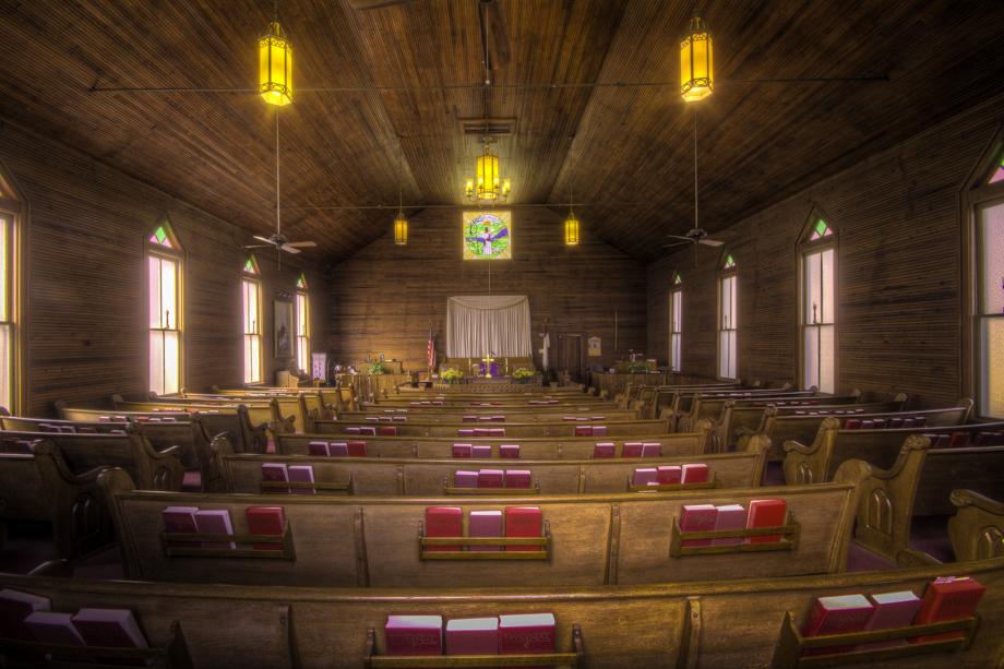 The interior of Dry Pond UMC includes wooden pews, horizontal wall and ceilings and warm yellow light from chandeliers. Photo by Scott MacInnis, courtesy Historic Rural Churches of Georgia.
