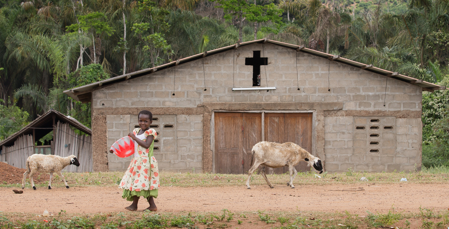 A young girl shares the road with passing goats in the fishing community of Monogaga.