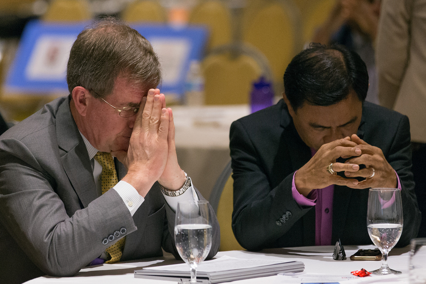 Bishops Scott J. Jones (left) and Rodolfo A. Juan pray during closing worship at the Council of Bishops meeting. Photo by Mike DuBose, UMNS.