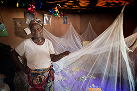 Matilda Ndanema displays the insecticide-treated mosquito net she received from the United Methodist Church's Imagine No Malaria campaign in 2010 at her home in Bumpe, near Bo, Sierra Leone. The insecticide is nearing the end of its useful life and several villages in the Bo district will receive new nets from the campaign in the first planned redistribution to replace the nets given in 2010. Photo by Mike DuBose, UMNS.