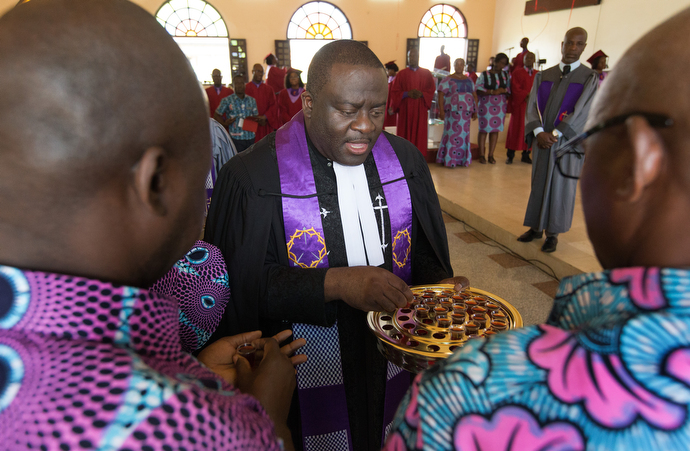 The Rev. Jean Claude Masuka Maleka serves Holy Communion during worship at Nazareth United Methodist Church. Photo by Mike DuBose, UMNS.