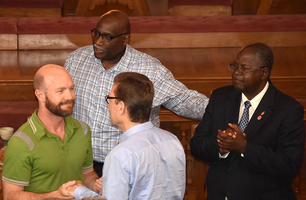 Matt Berryman and the Rev. Thomas Lambrecht, at left, talk during the closing of the last Commission on a Way Forward meeting.  Photo courtesy of Commission on a Way Forward Facebook page.