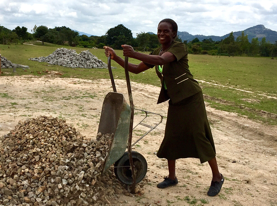 A woman dumps a load of rocks from a wheelbarrow while helping out at the construction site of the new Munyarari Mission health clinic in Mutare, Zimbabwe. Photo courtesy of Chabadza-Healing Hands Across Zimbabwe.