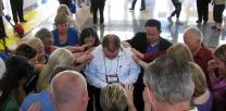 Church members pray over the Rev. Adam Hamilton. Photo by Sam Hodges, UMNS
