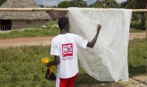 A Sierra Leonian volunteer with the Imagine No Malaria campaign checks on an insecticide treated mosquito net.