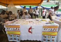 United Methodists, including Beatrice Gbanga (seated at table), medical and health coordinator for the church's Sierra Leone Annual Conference, help spread the word about Ebola during the kickoff for the national Maternal and Child Health Week at the soccer stadium in Bo, Sierra Leone, in June.