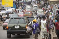 Vehicles and pedestrians make their way along a crowded street in Freetown, Sierra Leone.