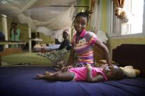 A young mother sits next to her baby who is being treated for malaria at Kissy Hospital.