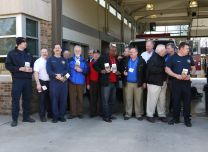 Conference presidents of UM Men and prayer advocates gather in front of two fire engines in Nashville, Tenn. after delivering devotional books. Photo courtesy United Methodist Men.