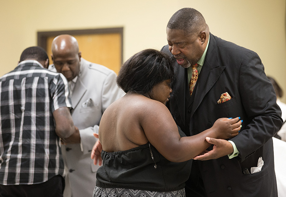 The Rev. Mark Windley (right) prays with parishioner Jada Roarx at Amazing Grace Community of Faith in Louisville, Ky. Photo by Mike DuBose, UMNS.