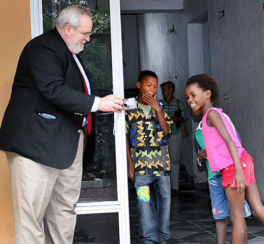 The Rev. Sam Dixon shares a digital photo with children during a visit to Kinshasa, Democratic Republic of the Congo, in December 2007.  A UMNS file photo by Ginny Underwood.