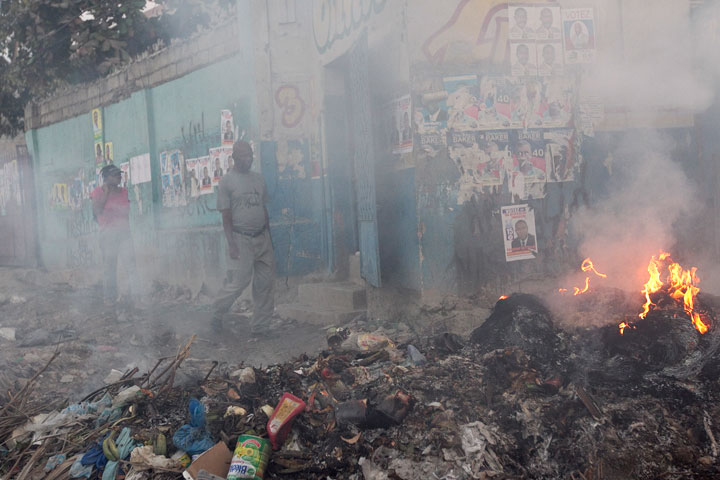 Residents make their way along walls covered with campaign posters and past piles of burning trash in the Carrefour neighborhood of Port-au-Prince.