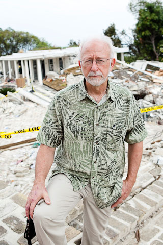 The Rev. James Gulley stands in front of the wreckage of the Hotel Montana. A UMNS photo by Jen Judge.