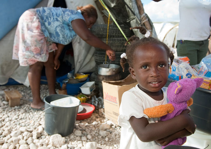Jeandline, 2, plays with a doll while her mother, Jean Marise, prepares dinner in front of their tent at Camp Corail.