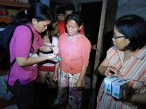 UMCom representative April Grace G. Mercado demonstrates how to use the Solio solar chargers to the youth in Ormoc City following Typhoon Haiyan, which struck the Philippines Nov. 8, 2013.