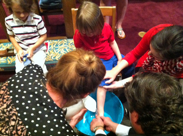 Children having their feet washed during Maundy Thursday worship.
