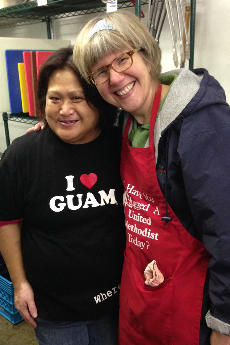 The Rev. Beth Estock poses in a kitchen with the head cook who volunteers to serve others.