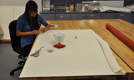Conservation Technician Jocelyn Chan covers the complex construction with layers of fabric for a finished appearance