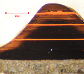 A fragment of lacquer ware in the 16th-century style examined in cross-section under the microscope proves to consist of over one hundred layers The design is black with three red stripes the brown edge is fading caused by light damage