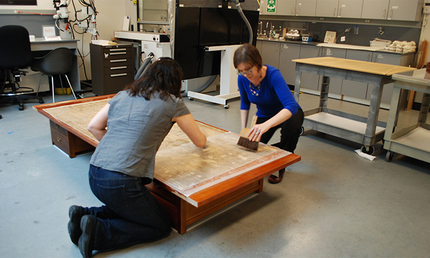 Jennifer Parson and Shiho Sasaki paper conservators applying new lining paper