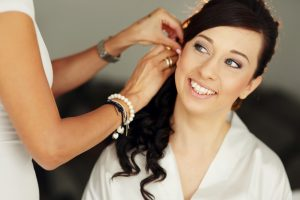 Stylist helping beautiful brunette happy bride to get ready for