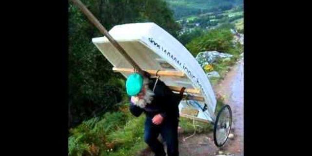 Piyanoyla dağa çıkan adam bu kez bir tekneyi sırtlamış