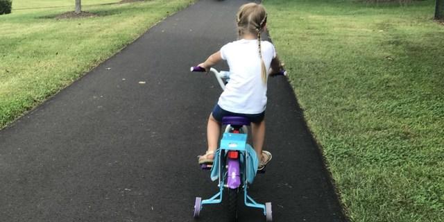 Dört tekerlekli bisikletin keyfini sürüyor
