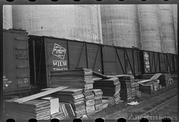 Freight cars at grain elevator with lumber used for...