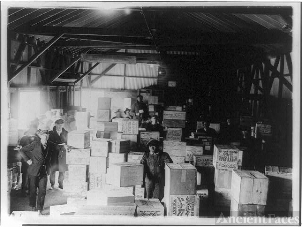 [Men standing in warehouse with cases of confiscated(?)...