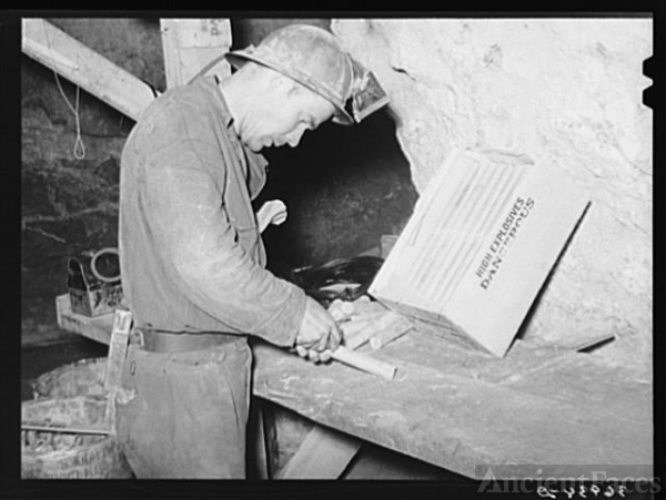 Miner inserting fuse into stick of dynamite. Mogollon,...