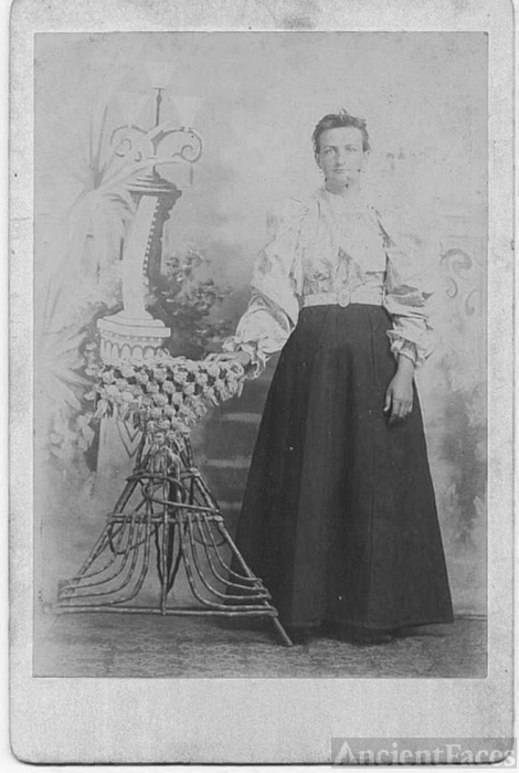 Lady Standing beside wicker table