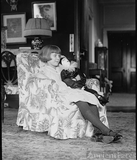 Girl seated in chair with doll