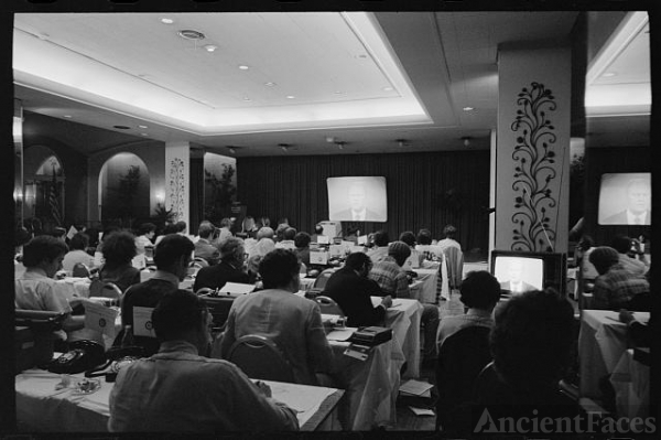 [Reporters in press room observe President Gerald Ford on...