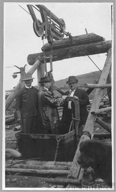 Frank G. Carpenter in middle of bucket at gold mine