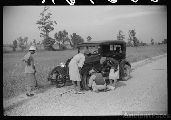 Repairing tire on road near Knowlton Plantation,...
