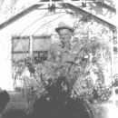 "Papa ""Pat"" Patterson in front of his wysteria bush"