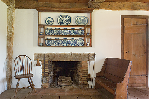 A seating arrangement around the dining room fireplace features a rare diminutive settle that was made around 1710 to 1720 and a Rhode Island Windsor chair. The rack above the fireplace is filled with choice pieces of the couple's extensive blue and white Canton collection. The rack itself was found with heavy old paint, which when removed, revealed the original bright bittersweet-colored paint.