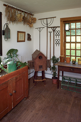 In the garden room antique rakes and other tools hang from the walls. A pin prick garden design on paper by the Schwenkfelders, a Pennsylvania German religious group, is also hung here. The dry sink is used as a planter. The room also holds some of the couple's collection of early Jaspe.