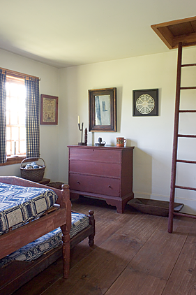 "This bedroom, which the couple refers to as the ""Hired Man's Room"" is furnished with an early matching low-post bedstead and early trundle bed with original red wash, purchased from Olde Hope Antiques. They are covered with early nineteenth-century woven coverlets. A one-drawer blanket chest retains its old red surface. A ladder, found in the spring house out back, leads up to the attic."