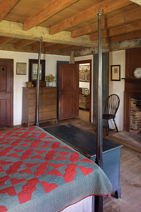 The eighteenth-century four-poster bedstead, covered by an Amish red and green quilt -- the wife's favorite -- covers the bed. A lift-top chest with original paint is at the foot of the bed. A piece of hairwork is hung beside the fireplace, above a Windsor chair. A New England tall chest of drawers retains its old surface.