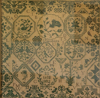 An English Quaker sampler worked in 1802 by Sarah Swinborn at the Ackworth School is one of five by daughters of the same family. It was worked with medallions and lettering, birds on branches, doves in pairs, and tulips and other flowers.
