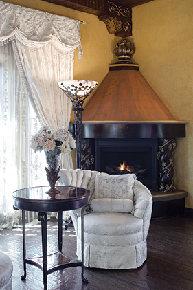 "A 1930s slipper chair, upholstered in silk damask, is one of a pair in the room. Says Sue, ""I had them in storage for twenty years, awaiting the perfect location; they were ideal for the space."" The corner fireplace features carved baroque-style columns and gold leaf trim."